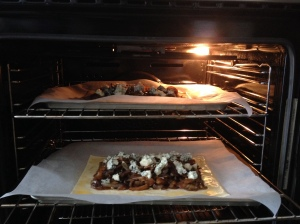 Two goat's cheese, stout and onion tarts in the oven.
